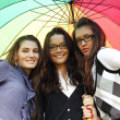 Smiling girlfriends under umbrella - Lizenzfreies Foto