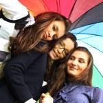 Smiling girlfriends under umbrella — Stock Photo #6669821