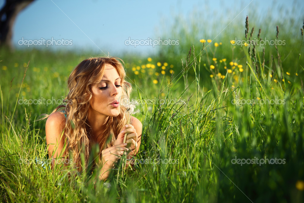 Blonde lays and blow on dandelion — Stock Photo #6668945