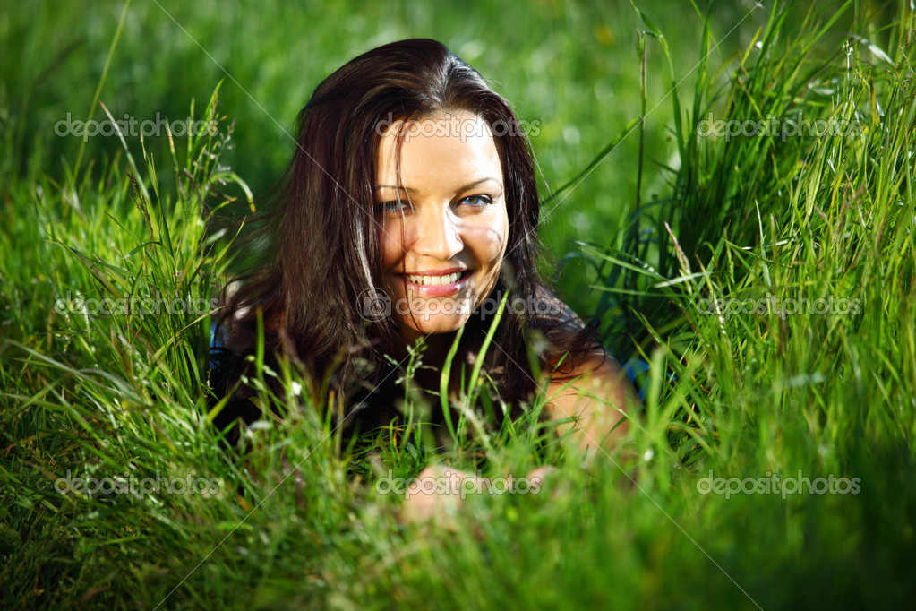 Brunette lays on green grass — Stock Photo #6668986