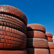Royalty-Free Stock Photo: Racetrack fence of white and red of old tires and female legs in boots