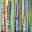 Lots of colorful glass and stone beads hanging in a row — Stock Photo