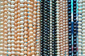 A lot of pearl beads hanging in a row — Stock Photo