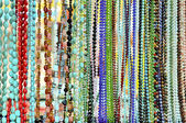 Lots of colorful glass and stone beads hanging in a row — Стоковое фото