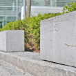 Rectangular granite fence in front of bushes — Stock Photo