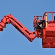 Red hydraulic construction cradle against the blue sky — Stock Photo #5813653