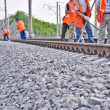 Stock Photo: Railway embankment, rails and workers in orange vests