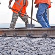 Railway embankment, rails and workers in orange vests — Stock Photo #6225222