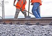 Railway embankment, rails and workers in orange vests — Stock Photo