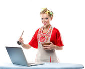 Woman is cooking with the recipe on a laptop — Stock Photo