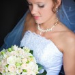 Close-up of a pretty bride with a bouquet of flowers - Stockfoto