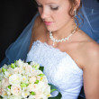 Close-up of a pretty bride with a bouquet of flowers - Stock Photo