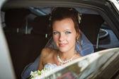 Portrait of a pretty bride in a car — Stock Photo