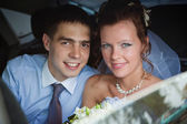 Portrait of a newlywed couple in a car — Stock Photo
