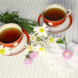 Two red mugs with camomiles and pink wild flowers - Stock Photo