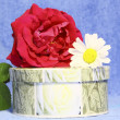 Stock Photo: A round box with a gift, a rose and a camomile on a blue background