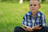 Boy with a book in the park — Stock Photo