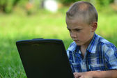 Boy with a laptop in the park — Stock Photo