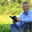 Portrait of a man in a park with a book — Stock Photo