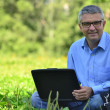 Portrait of a man in a park with a laptop — Stock Photo
