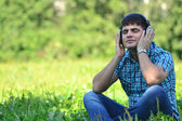 Portrait of a man in a park with headphones — Stock Photo