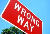 Wrong way road sign on a blue sky background — Stock Photo