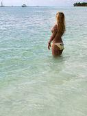 Mulher bonita de biquini tomando sol no mar — Fotografia Stock