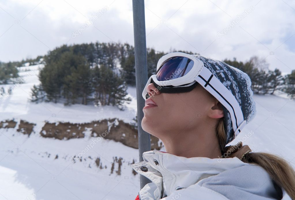 Portrait of beautiful skier in ski lift looking at sky — Stock Photo #5559979