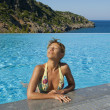 Beautiful woman suntanning in swimming pool — Foto Stock