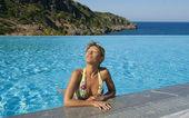 Beautiful woman suntanning in swimming pool — Stock Photo