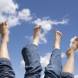 Stock Photo: Two sets of feet in air.