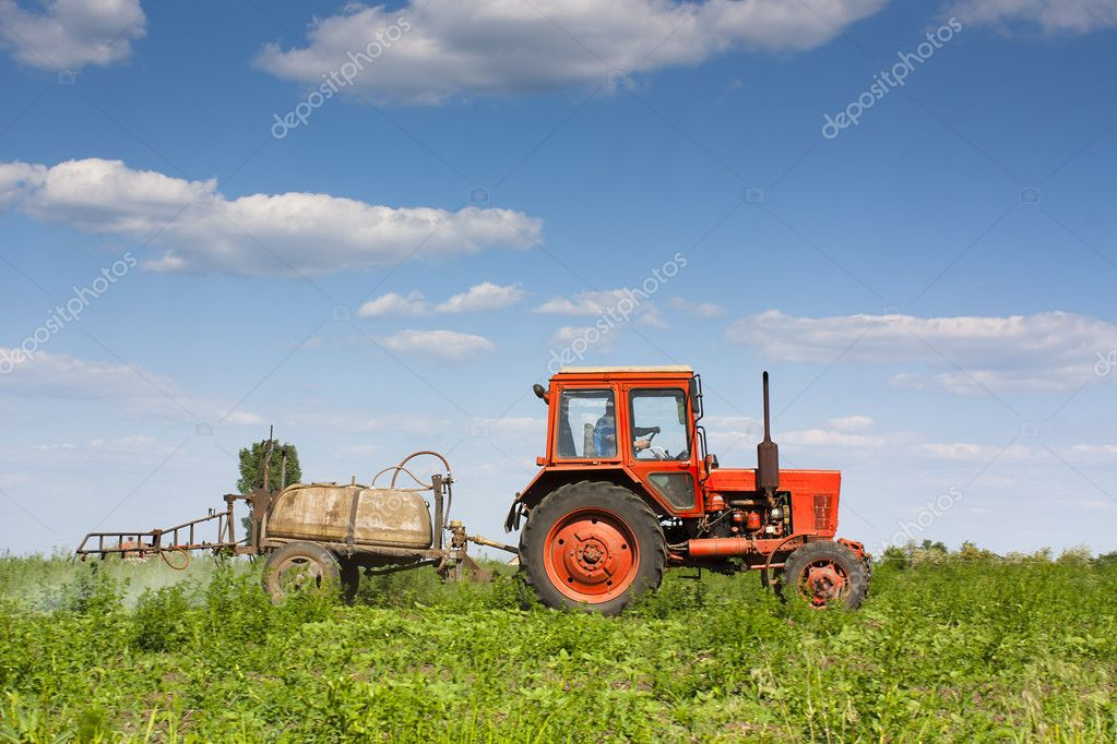 An old red tractor spraying crops with pesticide — Stock Photo #5609350