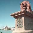 Lion statue guarding the blue danube and the Hungarian parliamen — Stock Photo
