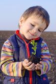 μικρό αγόρι στο γήπεδο κρατώντας το φυτό — 图库照片