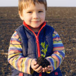 Smiling little boy on field holding the plant — Stock Photo #5565048