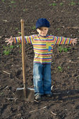 Little boy with big shovel in the field — Stock Photo