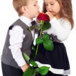 Two little children with red rose - Stock Photo