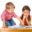 Two smiling children reading book on the desk — Stock Photo