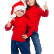 Two children with thumbs up sign and Santa's hats — Stock Photo