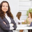 Successful business woman standing with her staff in background at office — Stock Photo #6725437