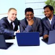 Interracial business team working at laptop in a modern office — Stock Photo #6727828