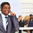 Portrait of a smiling businessman with headsets on in a call centre — Stock Photo