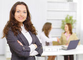 Successful business woman standing with her staff in background at office — Stock Photo
