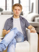 Portrait of the young man in white on sofa — Stock Photo