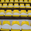 Football stadium tribune yellow chairs and snow — Stock Photo
