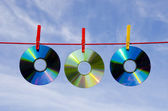 Three dvd and cd disks and sky — Stock Photo