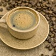 A Cup of Coffee with a Saucer and Coffee Beans on the Sacking — Stock Photo