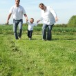 Stock Photo: Young family with toddler running across field together
