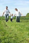 Young family with a toddler running across the field together — Stock Photo