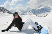Laughing young woman sitting in snow with snowboard — Stock Photo